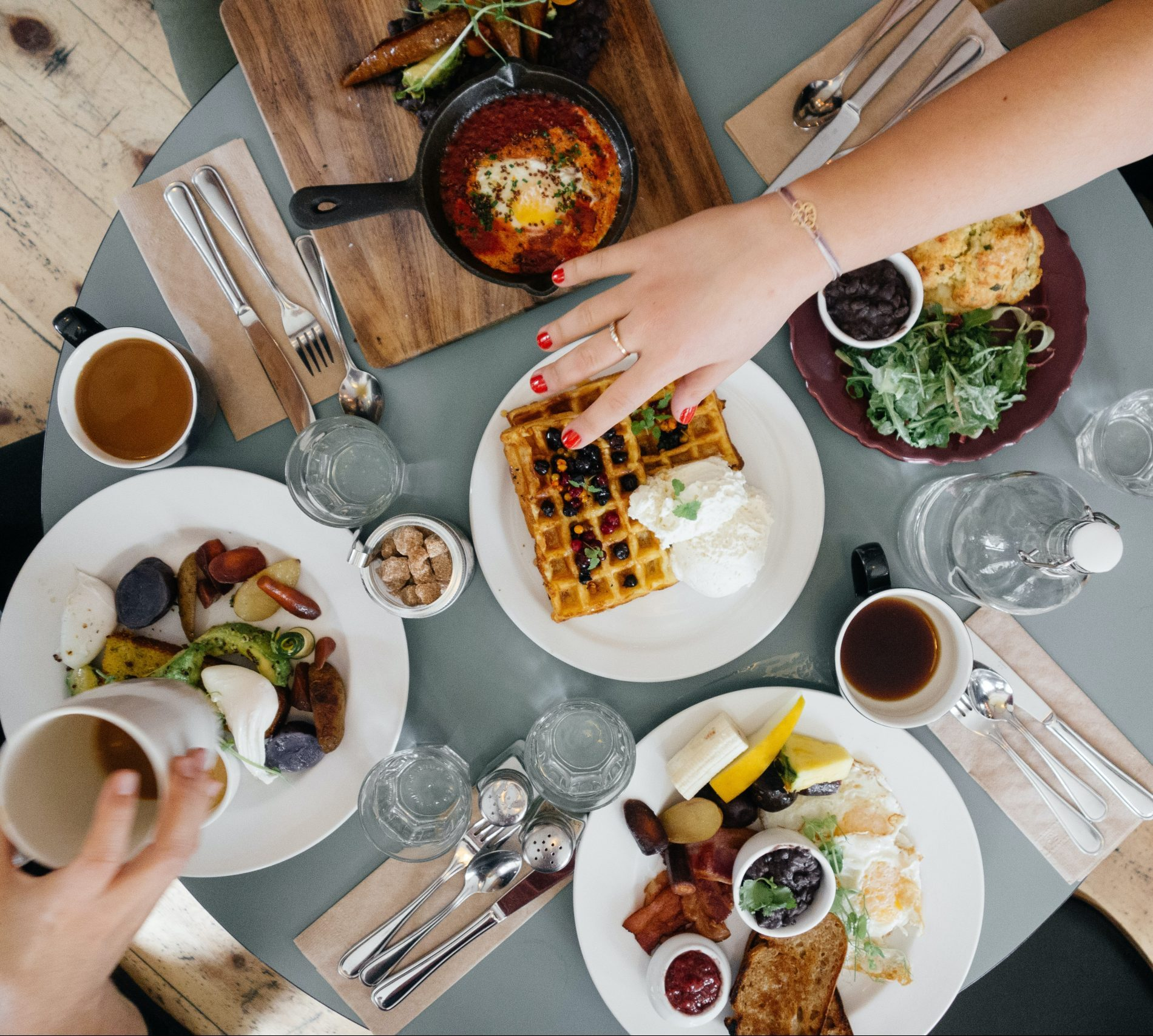 Photo from above of plates of food and hands reaching